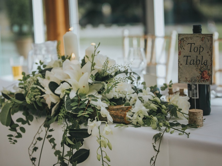 Simple top table or ceremony flowers adding a rustic feel.